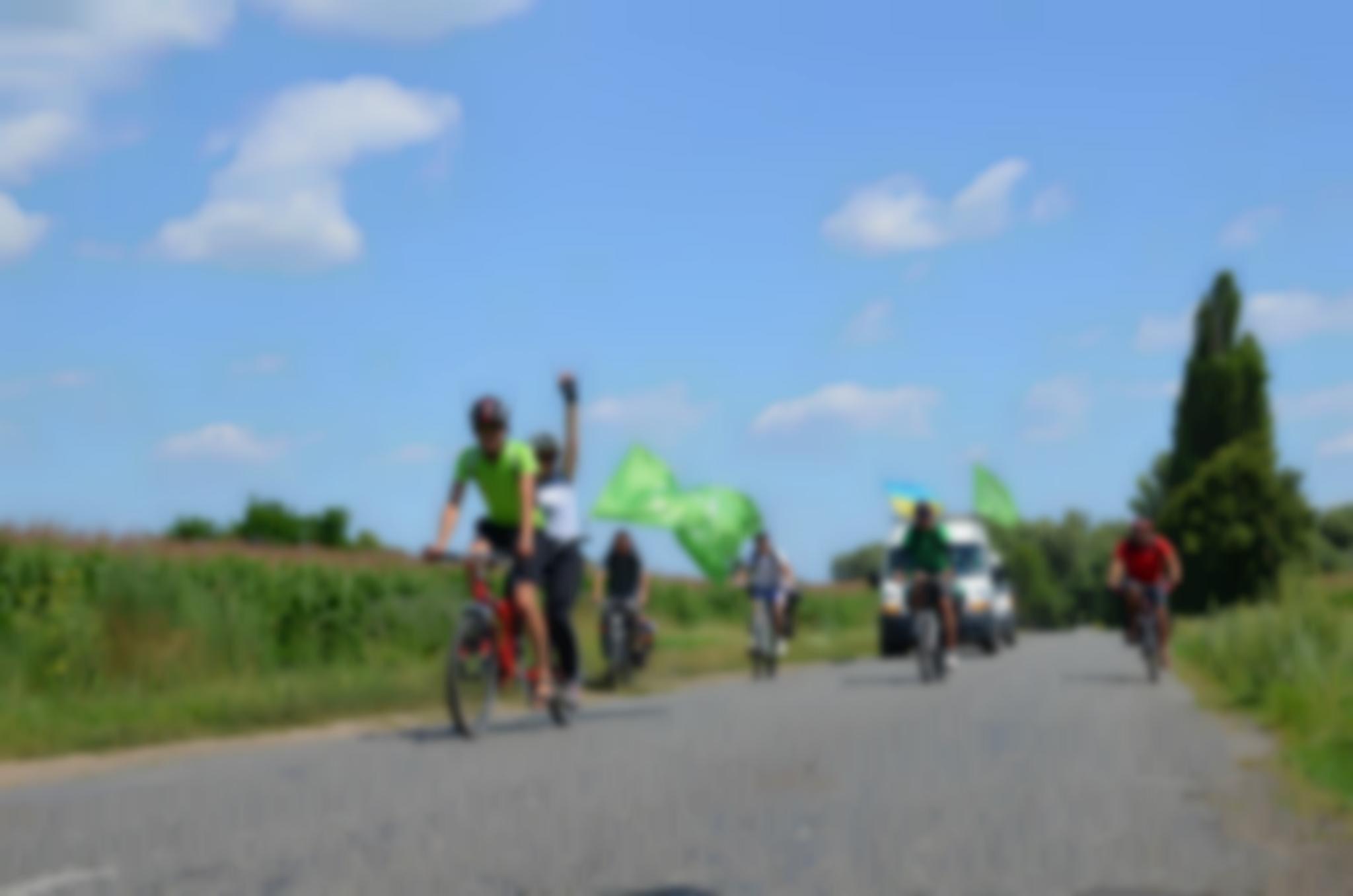 Розмите зображення, на ньому - рух колони велосипедистів з тандемами і прапорами велопробігу
