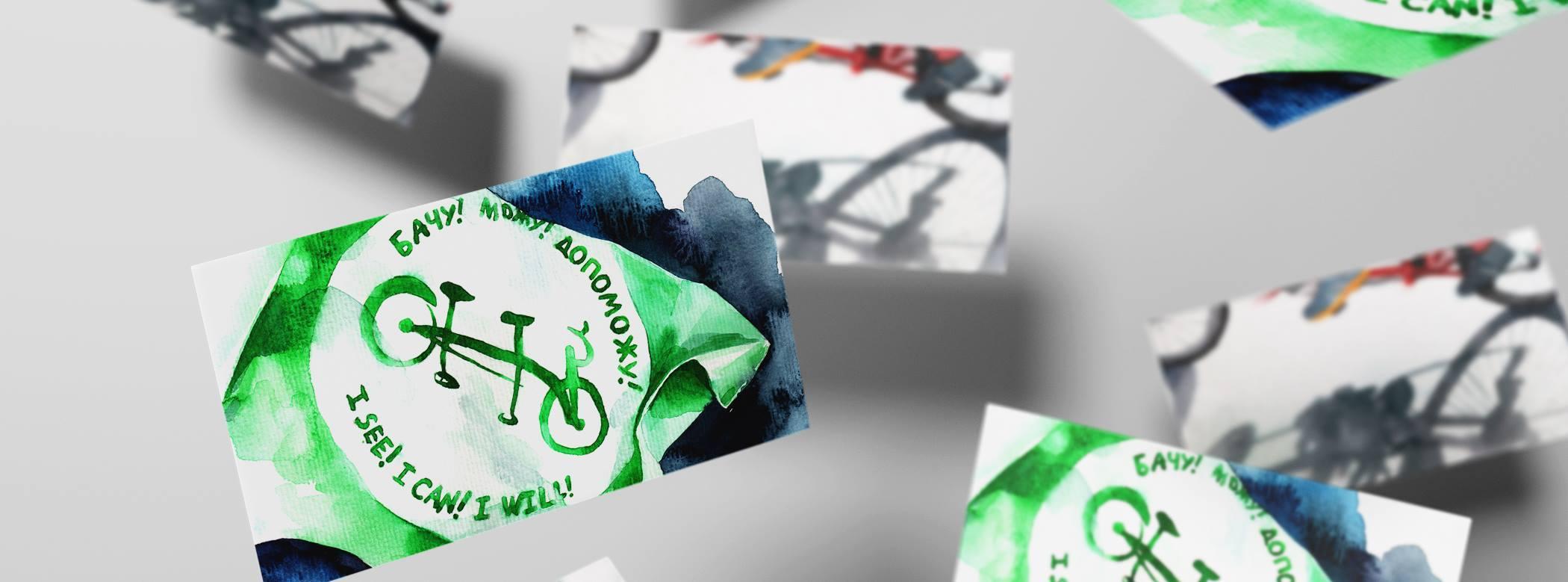 На фото: стилізовані листівки велопробігу літають у повітрі. На листівках альбомного формату - намальований аквареллю логотип велопробігу