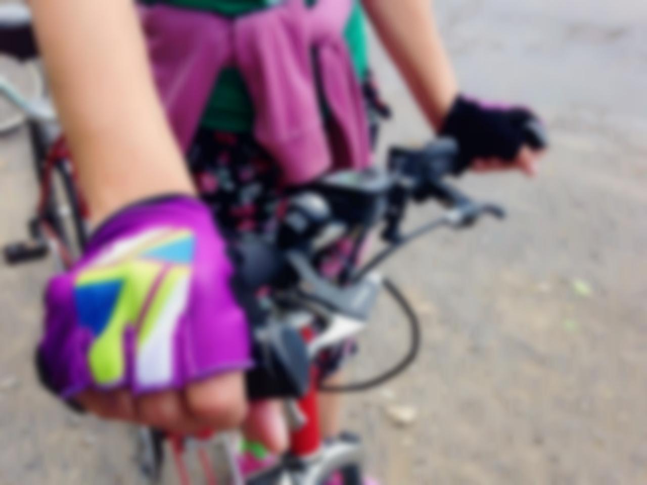 На розмитому фото: руль велосипеда та рука у фіолевій велорукавиці на ньому