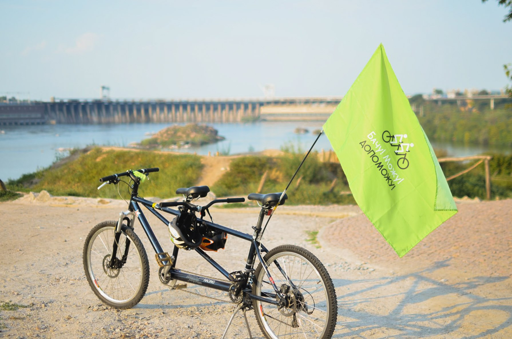 """A black tandem bicycle having a green banner with the writing """"I see! I can! I will!"""" in Ukrainian is standing on a path. In the background there is a river and a barrage."""