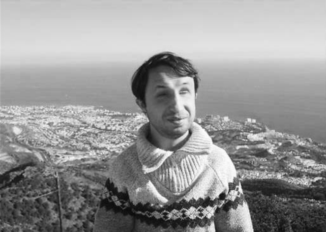 The picture is in black and white. A man is standing on a hill. He is wearing a pullover. His hair is dark. In his back there is a city and a coast. The sun is shining.