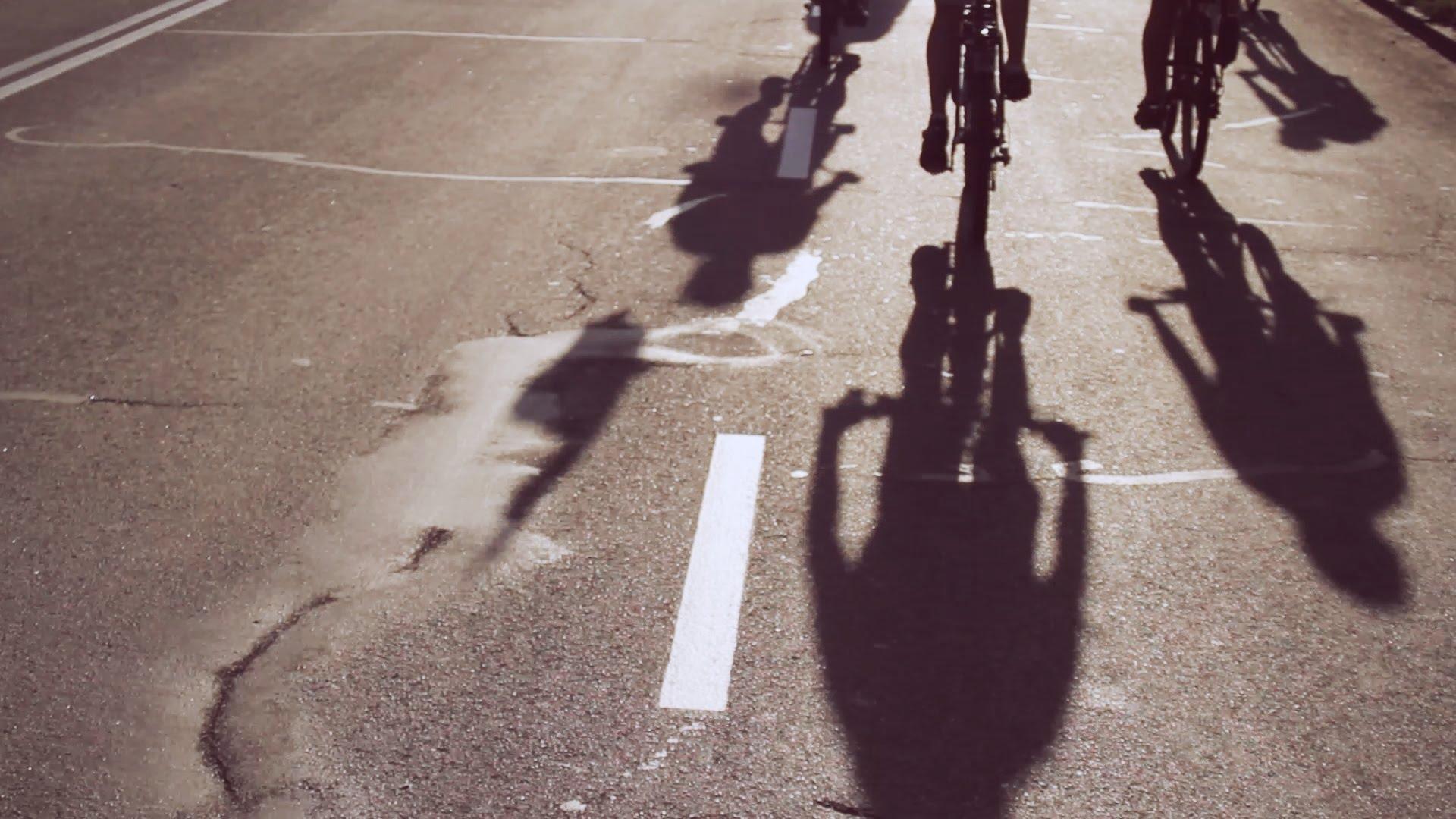 Асфальтова дорога, на ній довгі тіні від велосипедів, що їдуть назустріч