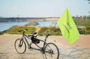 Чорний велосипед тандем із зеленим прапором, на якому пише українською мовою «Бачу! Можу! Допоможу!» стоїть на стежці. На задньому плані - річка та паркан